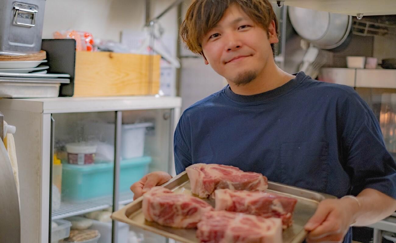 自慢の豚肉を見せる、倉持信宏さん